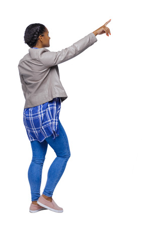 Side view of a young black girl in jeans and a checkered shirt. going girl showing.  backside view of person.  Rear view people collection. Isolated over white background. African American in a jacket goes with a finger up