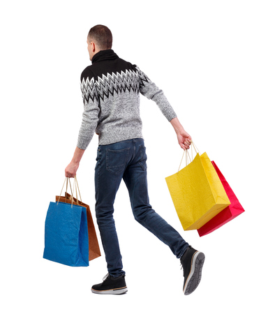 Side view of going man with shopping bags. guy in motion. backside view of person. Rear view people collection. Isolated over white background. A man in a sweater with lots of shopping.