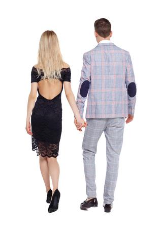 Rückansicht von zwei gehenden Geschäftsleuten. Rückansicht Menschen Sammlung. Rückansicht der Person. Getrennt über weißem Hintergrund. Stilvolles Paar bewegt sich Händchen haltend weg. Standard-Bild