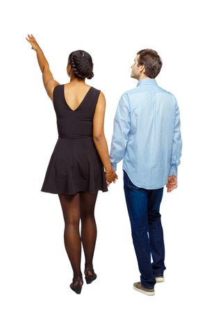 Back view of interracial going couple who points somewhere. walking friendly girl and guy holding hands. Rear view people collection. backside view of person. Isolated over white background. Multi-ethnic couple holding hands leaves with hand up.