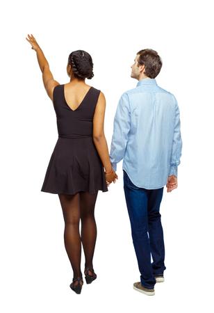 Vue arrière d'un couple interracial qui pointe quelque part. marche sympathique fille et gars se tenant la main. Collection de personnes vue arrière. vue arrière de la personne. Isolé sur fond blanc. Un couple multiethnique se tenant la main part avec la main vers le haut.