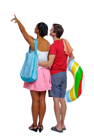 Back view of a an international pointing couple with an inflatable circle and beach accessories. beautiful friendly girl and guy together. Rear view people collection.  backside view of person.  Isolated over white background. Young multinational couple looking at something above 版權商用圖片