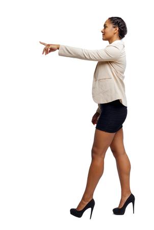 Vista lateral de un afroamericano negro con un traje que va y apunta con la mano. vista trasera de la persona. Colección de personas de vista trasera. Aislado sobre fondo blanco.