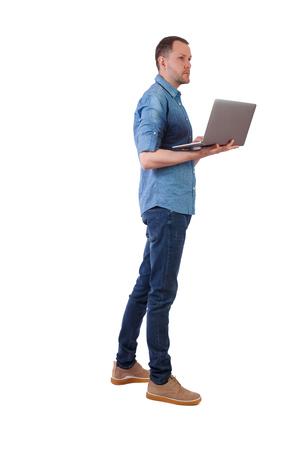 Achteraanzicht van een man die met een laptop staat. Achteraanzicht mensen collectie. achteraanzicht van persoon. Geïsoleerd op witte achtergrond. Een jonge ingenieur controleert informatie met een laptop.