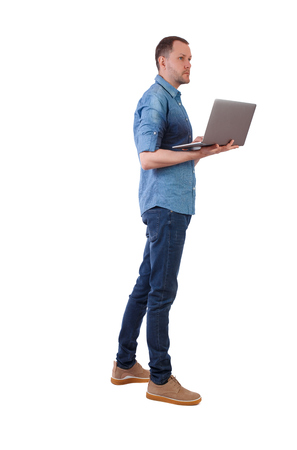 Back view of a man who is standing with a laptop. Rear view people collection. backside view of person. Isolated over white background. A young engineer checks information with a laptop.