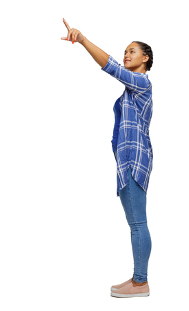Side view of a black African-American woman in a shirt pointing upwards. Rear view people collection. backside view of person. Isolated over white background.