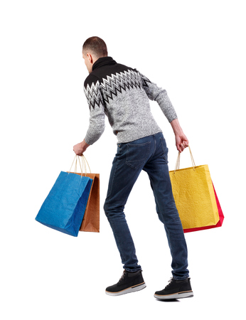 Side view of a man in a sweater with shopping bags that runs. backside view of person.  Rear view people collection. Isolated over white background. The guy in a warm gray sweater runs and rush to shopping.