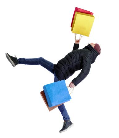 Homme tombant en veste d'hiver avec des sacs à provisions. Mec en mouvement. vue arrière de la personne. Collection de personnes vue arrière. Isolé sur fond blanc. Le gars qui porte la casquette et la veste qui glisse tombe en faisant ses courses.