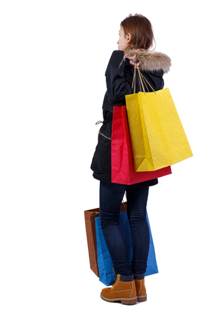 Side view of woman in winter jacket with shopping bags. backside view of person.  Rear view people collection. Isolated over white background. A girl in a warm jacket with fur is standing holding heavy shopping bags.