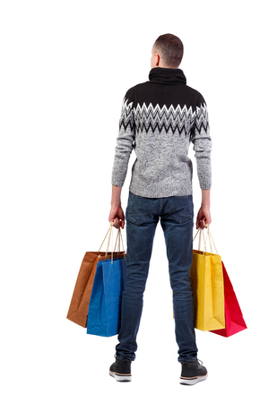 back view of man in winter sweater with shopping bags . beautiful brunette guy in motion.  backside view of person.  Rear view people collection. Isolated over white background.  A guy in a warm sweater holds four shopping bags.
