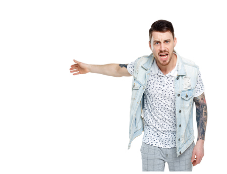 The man screams. Aggressive guy in tattoos yelling at the frame and showing his hands back. An angry guy scandals and understands the problems. Isolated on white background.