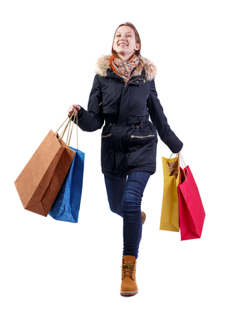 Front view of a happy woman in a jacket with shopping bags that runs. beautiful brunette girl in motion.  backside view of person.  Rear view people collection. Isolated over white background. A girl in a warm jacket with fur smiling runs to the meeting. Stok Fotoğraf