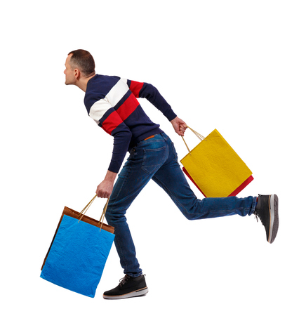 Side view of a man in a sweater with shopping bags that runs. backside view of person.  Rear view people collection. Isolated over white background. The guy on sale runs with shopping bags. Banque d'images