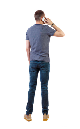 back view of business man talking on mobile phone. rear view people collection. Isolated over white background. backside view of person.  A man in a blue T-shirt talking on a smartphone. Imagens