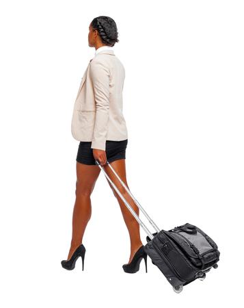 Rückansicht eines schwarzen Afroamerikaners in formeller Kleidung, der mit einem Koffer geht. Geschäftsfrau in Bewegung. Rückansicht der Person. Rückansicht Menschen Sammlung. Getrennt über weißem Hintergrund.
