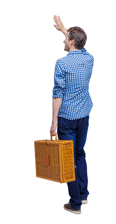 Back view of a man who comes with a suitcase for a picnic welcomes someone with his hand. backside view of person. Rear view people collection. Isolated over white background. Guy goes on a picnic welcoming friends Imagens