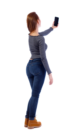 Back view of a woman who makes selfie with a smartphone. girl  watching. Rear view people collection.  backside view of person.  Isolated over white background. A young girl in a striped sweater holds a smartphone on an outstretched hand.