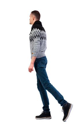 Vue latérale du bel homme en pull d'hiver. jeune homme marchant. Collection de personnes vue arrière. vue arrière de la personne. Isolé sur fond blanc. Un gars vêtu d'un pull gris chaud marche lentement sur le côté. Banque d'images