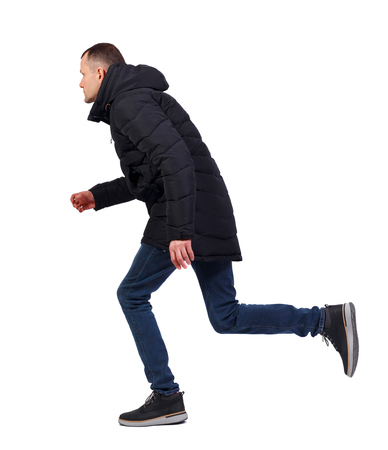 Side view of a running man in winter jacket. backside view of person.  Rear view people collection. Isolated over white background. The guy in the long black winter jacket runs past ducking.