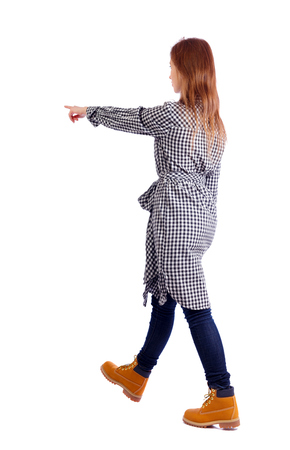 Side view of a girl walking with a pointing hand. going girl showing.  backside view of person.  Rear view people collection. Isolated over white background. A girl in a plaid dress walks past showing an arm forward. 版權商用圖片