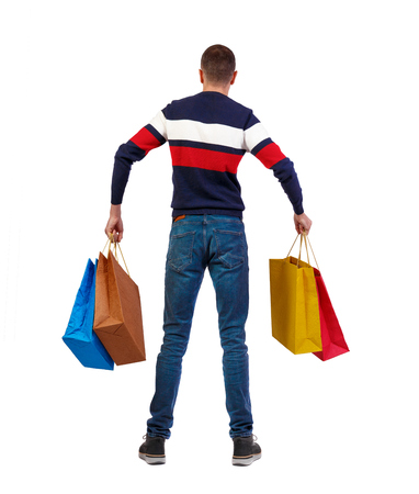 back view of man  with shopping bags . beautiful brunette guy in motion.  backside view of person.  Rear view people collection. Isolated over white background. The guy in the striped sweater is holding a bag in his hands.