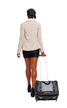 Vista posterior del afroamericano negro en traje formal caminando con una maleta. mujer de negocios en movimiento. vista trasera de la persona. Colección de personas de vista trasera. Aislado sobre fondo blanco. Foto de archivo