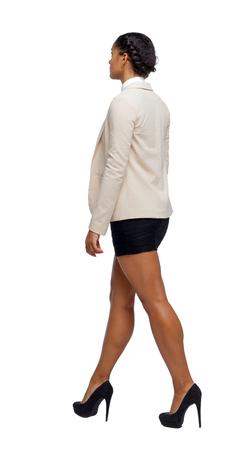 Seitenansicht eines schwarzen Afroamerikaners in einem Anzug, der zu seiner Hand passt. Rückansicht der Person. Rückansicht Menschen Sammlung. Getrennt über weißem Hintergrund. Geschäftsfrau in Schuhen mit hohen Absätzen geht voran.