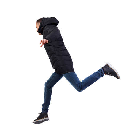 Side view of a man in a winter jacket who jumps. backside view of person.  Rear view people collection. Isolated over white background. The guy in the long black winter jacket jumps over a puddle.