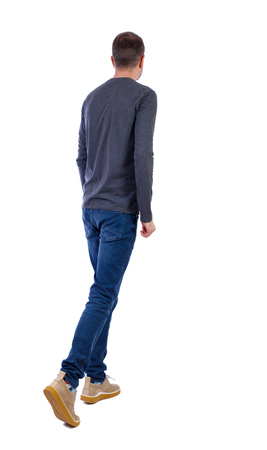 Back view of going  handsome man . walking young guy . Rear view people collection.  backside view of person.  Isolated over white background. A young guy in a gray sweater slowly goes forward.