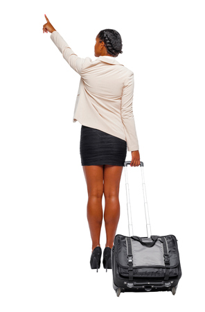 Back view of a black African-American in formal attire with a suitcase and pointing. business woman in motion.  backside view of person.  Rear view people collection. Isolated over white background.
