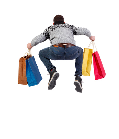 Back view of a jumping man in a sweater with shopping bags that runs. backside view of person.  Rear view people collection. Isolated over white background.