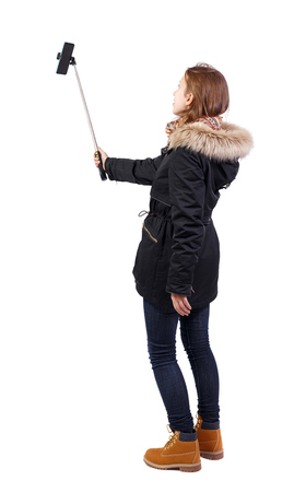 back view of standing young beautiful girl in winter jacket with smartphone in the hands of. Rear view people collection.  backside view of person. Isolated over white background. 版權商用圖片