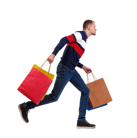 Side view of a man in a sweater with shopping bags that runs. backside view of person.  Rear view people collection. Isolated over white background. The guy in the striped sweater quickly runs with multi-colored bags.