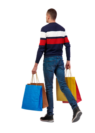 Side view of going man with shopping bags. guy in motion. backside view of person. Rear view people collection. Isolated over white background. A stylish man in a striped sweater comes with a lot of multi-colored paper shopping bags.