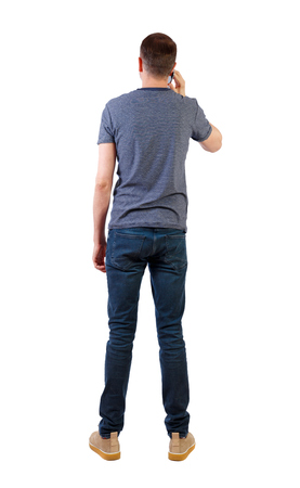 back view of a man talking on the phone. backside view of person.  Rear view people collection. Isolated over white background. A young businessman stands holding a smartphone near the ear. Фото со стока