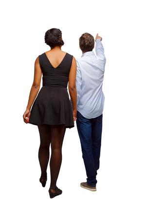 Rückansicht des interracial gehenden Paares, das irgendwo zeigt. zu Fuß freundliches Mädchen und Kerl, die Händchen halten. Rückansicht Menschen Sammlung. Rückansicht der Person. Getrennt über weißem Hintergrund. Mann und Mädchen auf einem Ausflug oder einer Ausstellung. Standard-Bild