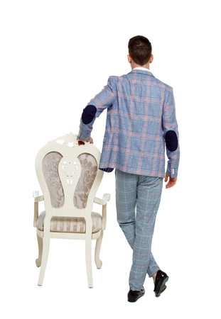 Back view of a man in an expensive stylish suit. Businessman leans on chair. Rear view people collection.  backside view of person.  Isolated over white background. A man and a chair. Imagens