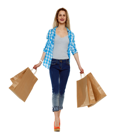 Front view of a woman walking with shopping bags. beautiful girl in motion.  Frontside view of person.  Shopping  people collection. Isolated over white background. Happy woman with shopping. Stok Fotoğraf
