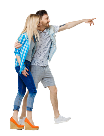 Side view of the couple walking and pointing upwards. Rear view people collection. backside view of person. Isolated over white background. The guy and the girl embracing laugh