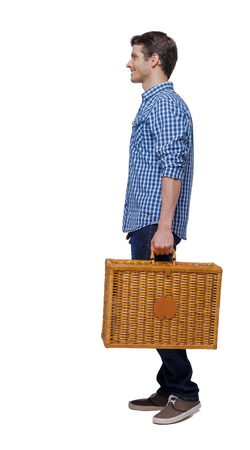 Side view of a man walking with a picnic bag. backside view of person.  Rear view people collection. Isolated over white background. Stylish guy with a wicker suitcase smiling.