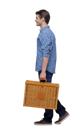 Side view of a man walking with a picnic bag. backside view of person.  Rear view people collection. Isolated over white background. Stylish guy with a wicker suitcase is smiling.