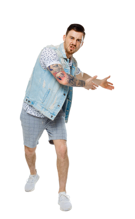 The man screams. Aggressive guy in tattoos yelling at the frame and showing his hands back. An angry guy scandals and understands the problems. Isolated on white background. The guy in the denim vest annoyed shows back. Imagens