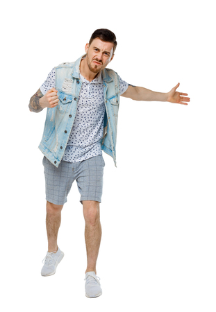 The man screams. Aggressive guy in tattoos yelling at the frame and showing his hands back. An angry guy scandals and understands the problems. Isolated on white background. Unhappy guy in denim jacket shows his hand back.