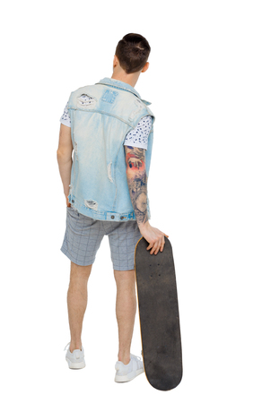 Back view of a man in shorts with a skateboard. A guy posing with a board for skating. Rear view people collection.  backside view of person.  Isolated over white background. Unhappy guy in denim jacket is leaning on skate.