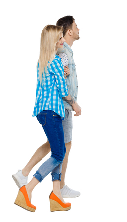 Side view of going couple. walking friendly girl and guy holding hands. Rear view people collection. backside view of person. Isolated over white background. The couple is embracing. Imagens