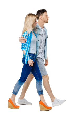 Side view of going couple. walking friendly girl and guy holding hands. Rear view people collection. backside view of person. Isolated over white background. Guy hugging the shoulders of a girl goes forward.