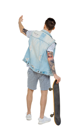 Back view of a pointing man with a skateboard. Rear view people collection.  backside view of person.  Isolated over white background. Guy leaning on a skate waving his hand.