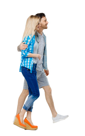 Side view of going couple. walking friendly girl and guy holding hands. Rear view people collection. backside view of person. Isolated over white background. The guy and the girl go embracing and smiling.