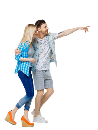 Side view of the couple walking and pointing upwards. Rear view people collection. backside view of person. Isolated over white background. The guy and the girl go laughing