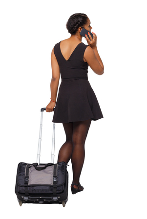 Back view of a black African-American with a suitcase with smartphone. backside view of person.  Rear view people collection. Isolated over white background. Traveler with a suitcase calls a taxi. Imagens